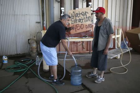 Pastor Frankie Olmedo, 56, (L) who volunteers four hours a day to hand out water, fills up a container for Luis Bocanegra, 35, in Porterville, California October 14, 2014. REUTERS/Lucy Nicholson