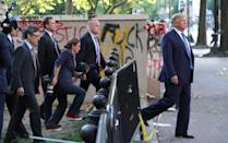 U.S. President Trump walks past a building defaced with graffiti by protestors in Washington