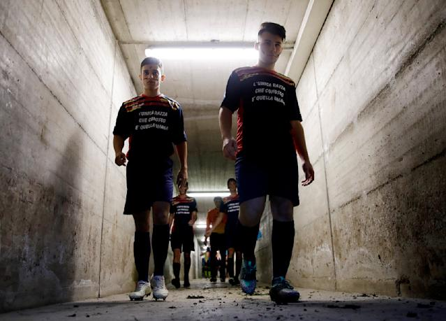 """Desio soccer players walk in the tunnel leading to the pitch with their faces painted with black marks and wearing jerseys reading """" The only race I know is the human one"""" before a youth team soccer match between Desio and Sovicese at the municipal stadium in Desio, near Milan, Italy, Saturday, Nov. 9, 2019. The initiative comes a week after a 10-year-old member of the Aurora Desio team was allegedly subjected to racist abuse during a match. (AP Photo/Luca Bruno)"""