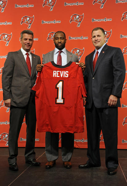 NFL football cornerback Darrelle Revis, center, is joined by Tampa Bay Buccanners general Manager Mark Dominik, left, and head coach Greg Schiano as he holds up a Tampa Bay Buccaneers jersey after addressing the media announcing that he and the Buccaneers have agreed on a six-year contract during a press conference Monday, April, 22, 2013, in Tampa, Fla. The Buccaneers acquired Revis from the New York Jets in exchange for their first-round pick in the 2013 NFL Draft and a conditional selection in the 2014 NFL Draft. (AP Photo/Brian Blanco)