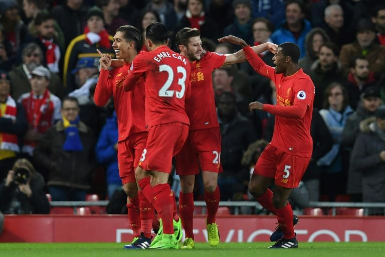 Liverpool's midfielder Roberto Firmino (L) celebrates with teammates after scoring the opening goal of the English Premier League football match against Arsenal March 4, 2017