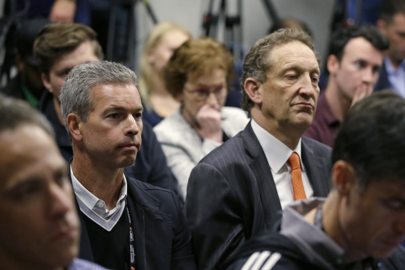 San Francisco Giants board member Rob Dean, left, and CEO Larry Baer, right, listen during a news conference introducing new manager Gabe Kapler at Oracle Park Wednesday, Nov. 13, 2019, in San Francisco. Gabe Kapler has been hired as manager of the San Francisco Giants, a month after being fired from the same job by the Philadelphia Phillies. Kapler replaces Bruce Bochy, who retired at the end of the season following 13 years and three championships with San Francisco. (AP Photo/Eric Risberg)