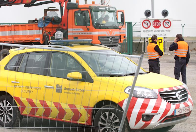 Airport security officers stand near a fence that was cut next to the tarmac, at Brussels international airport, Tuesday, Feb. 19, 2013. Police on Tuesday were looking for eight men who made a hole in a security fence of Brussels' international airport, drove onto the tarmac and robbed tens of millions of dollars worth of diamonds from the hold of a Swiss-bound plane. (AP Photo/Yves Logghe)