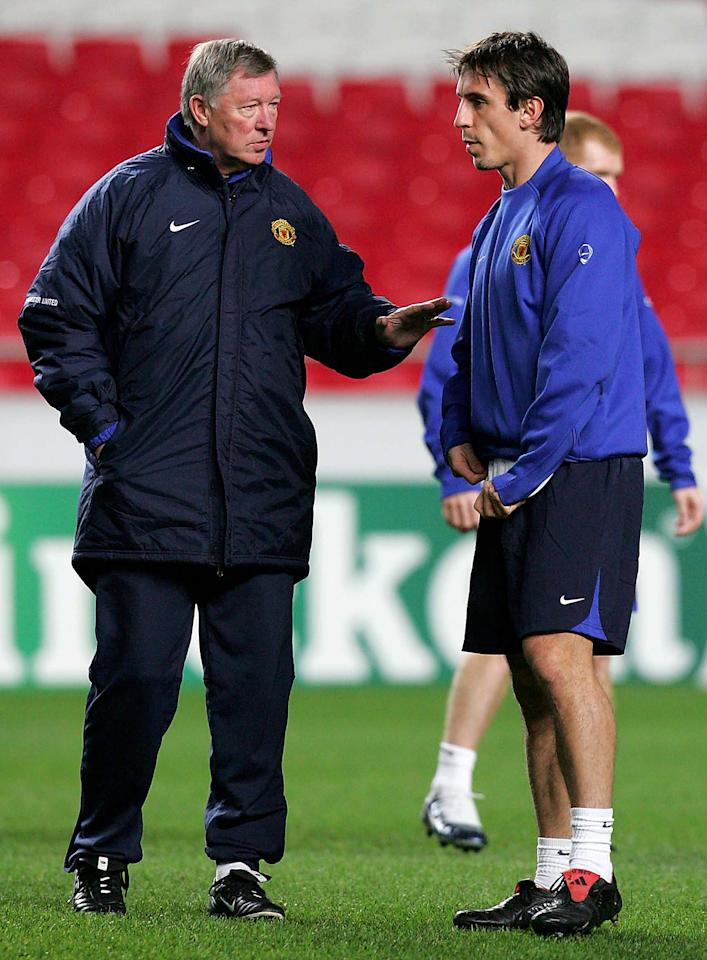 LISBON, PORTUGAL - DECEMBER 6: Sir Alex Ferguson of Manchester United talks to Gary Neville during a training session ahead of the UEFA Champions League match between Benfica and Manchester United on December 6, 2005 in Lisbon, Portugal. (Photo by Matthew Peters/Manchester United via Getty Images)