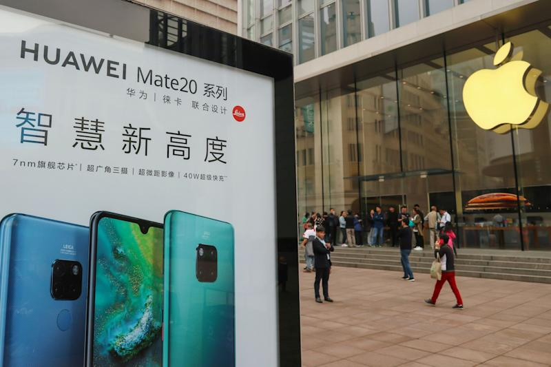 An advertisement for Huawei Mate 20 series is seen outside an Apple store, as customers queue before the store opens on the day the new iPhone XR goes on sale in Shanghai, China October 26, 2018. REUTERS/Stringer ATTENTION EDITORS - THIS IMAGE WAS PROVIDED BY A THIRD PARTY. CHINA OUT.