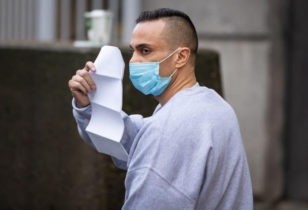 Mohammad Movassaghi tries to hide his face with a copy of his release order after his arrest on Jan. 31. He was sentenced to time served and probation for violating public health orders by turning his downtown penthouse into a nightclub during the COVID-19 pandemic. (Darryl Dyck/The Canadian Press - image credit)