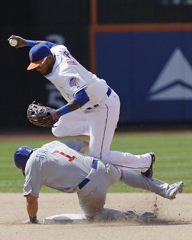 New York Mets Jordany Valdespin, top, jumps to avoid Chicago Cubs' Cody Ransom after forcing him out at second base during the seventh inning of a baseball game Saturday, June 15, 2013, in New York. The Cubs' Starlin Castro was safe at first. (AP Photo/Frank Franklin II)