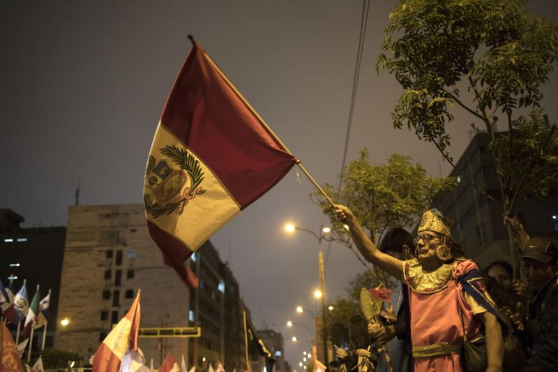 A supporter of Peruvian President Martin Vizcarra waves his nation's flag outside Congress after Vizcarra dissolved the legislature in Lima, Peru, Monday, Sept. 30, 2019. Opposition legislators defied Vizcarra's order dissolving congress by voting to suspend him from office and swearing in Vice President Mercedes Araoz as the South American nation's new leader. (AP Photo/Rodrigo Abd)