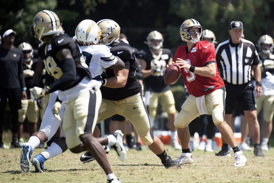 New Orleans Saints quarterback Drew Brees, right, looks to throw a pass during a joint NFL football practice with the Los Angeles Chargers in Costa Mesa, Calif., Thursday, Aug. 15, 2019. (AP Photo/Kyusung Gong)