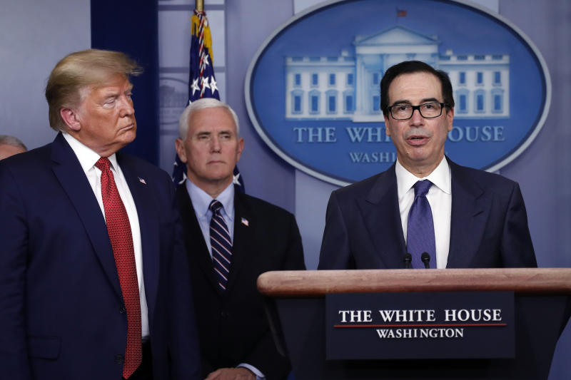 Treasury Secretary Steven Mnuchin speaks as President Donald Trump and Vice President Mike Pence listen during a briefing about the coronavirus in the James Brady Briefing Room, Wednesday, March 25, 2020, in Washington. (AP Photo/Alex Brandon)