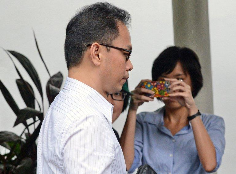 Ex-director of the Central Narcotics Bureau Ng Boon Gay (left) arrives for a hearing at the subordinate court in Singapore on February 14, 2013. Ng was cleared of corruption on Thursday after a court rejected charges that he demanded oral sex from a contractor to help her win government deals