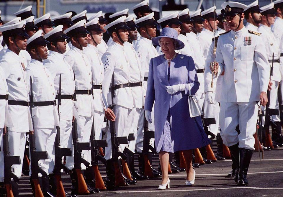<p>The queen wore a purple dress, tonal coat and wide-brimmed hat, white heels, and a pair of white gloves for a royal visit to Cape Town, South Africa.</p>