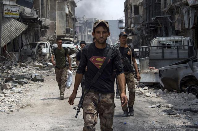 <p>An Iraqi member of the Counter-Terrorism Services (CTS) wearing a superman T-shirt walks in the Old City of Mosul on July 3, 2017 during an ongoing offensive to retake the city from Islamic State (IS) group fighters. (Photo: Fadel Senna/AFP/Getty Images) </p>