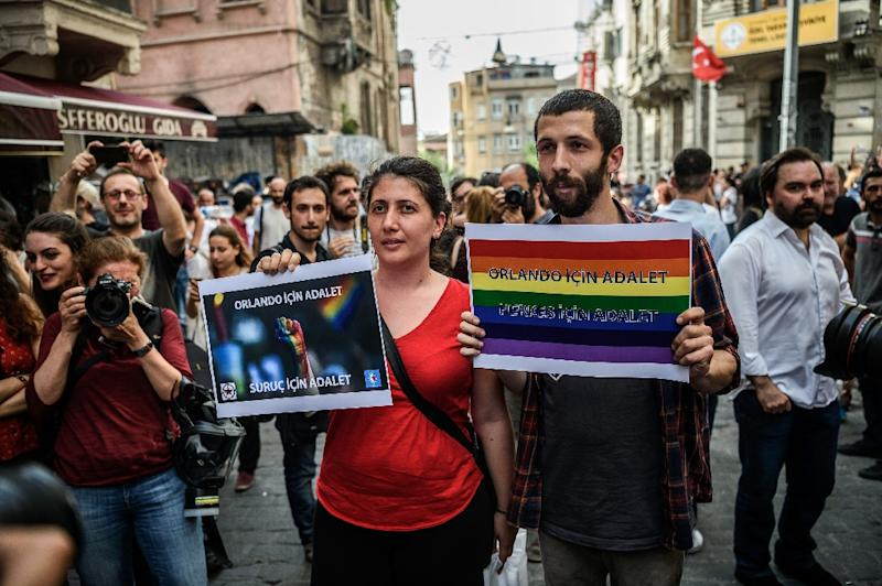 "People hold signs reading ""Justice for Orlando"" during a rally staged by the LGBT community on Istiklal avenue in Istanbul on June 19, 2016 (AFP Photo/Ozan Kose)"