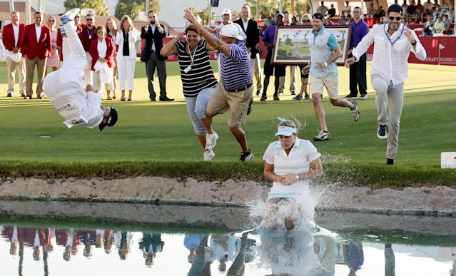 Lexi Thompson jumps into Poppy's Pond after winning the Kraft Nabisco Championship golf tournament Sunday, April 6, 2014, in Rancho Mirage, Calif. (AP Photo/Chris Carlson)