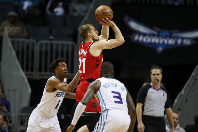 Toronto Raptors guard Matt Thomas, center, shoots a jumper as Charlotte Hornets guards Malik Monk (1) and Terry Rozier (3) watch during the first half of an NBA basketball game in Charlotte, N.C., Wednesday, Jan. 8, 2020. (AP Photo/Nell Redmond)