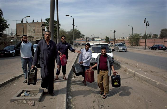 Egyptian public transportation drivers carry empty fuel containers after failing to fill them up from a nearby gas station, on the outskirts of Cairo, Egypt, Monday, March 11, 2013. On Sunday, drivers of Cairo's popular communal taxis staged a strike to protest fuel shortages, creating a traffic nightmare on the already congested streets of the city. Some of the drivers, armed with knives and firearms, attacked others who did not observe the strike or got into fights with motorists angered by their action. (AP Photo/Nasser Nasser)