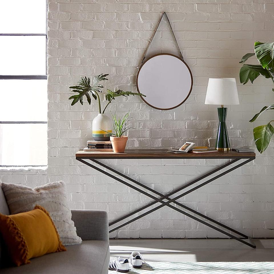 <p>Hang this <span>Rivet Casual Round Mirror</span> ($65) in your entryway.</p>