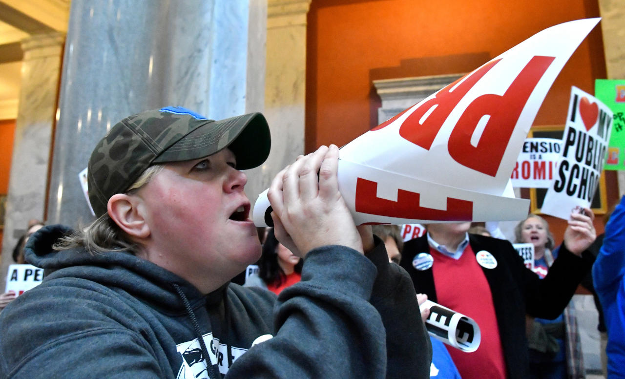 FILE - In this March 9, 2018, file photo, Nema Brewer, an employee of the Fayette County School District, uses a protest sign as a makeshift bullhorn to shout at the Kentucky Senate chambers in protest of Kentucky Senate Bill 1, in Frankfort, Ky. The public education uprisings that began in West Virginia and spread to Arizona, Oklahoma and Kentucky share similar origin stories. Teachers, long tired of low wages and a dearth of state funding, begin talking to each other online. Their Facebook groups draw tens of thousands of members. They share stories of their frustrations and then they demand change. (AP Photo/Timothy D. Easley, File)