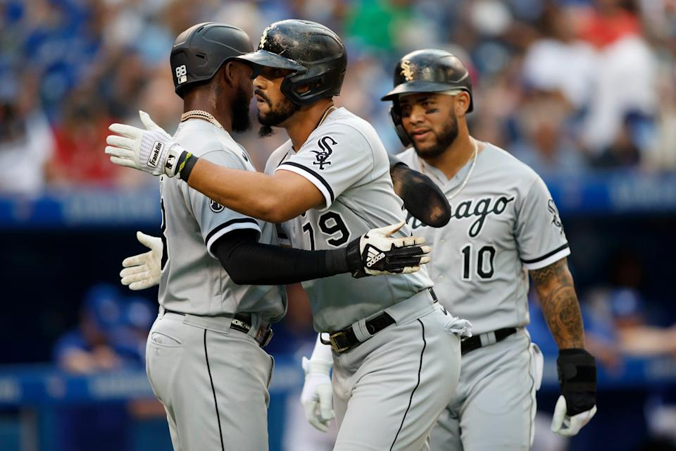 Jose Abreu (79) of the Chicago White Sox celebrates at the plate with Luis Robert (88) and Yoan Moncada (10) after hitting a three-run home run.