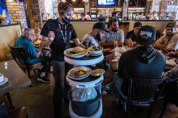 A waitress at Sergio's takes control of the Servi robot, known as ASTRO, and steers it manually using the keyboard to guide it around a spot it can't get through because a diner inadvertently blocked its path with his chair.