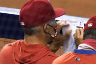 Philadelphia Phillies manager Joe Girardi looks at the lineup during the fourth inning of a baseball game against the Miami Marlins, Monday, Sept. 14, 2020, in Miami. (AP Photo/Lynne Sladky)