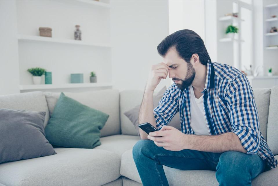 sad frustrated man with stubble in jeans, shirt holding fingers between close eyes using smart phone