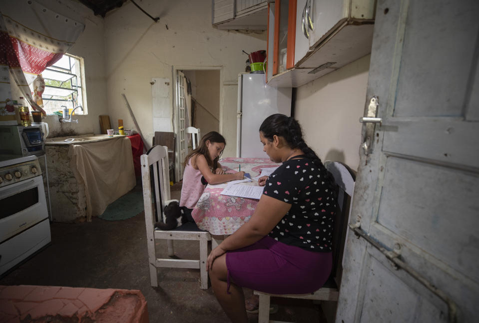 Amanda Trindade helps her 9-year-old daughter Giovana with her homework that was dropped off by a school worker at their home in the rural area in Sao Jose dos Campos, Brazil, Tuesday, July 14, 2020. In March when schools closed due to the COVID-19 pandemic, the Mother Teresa school decided to deliver homework to students because most of them don't have computers or have very limited Internet access. (AP Photo/Andre Penner)