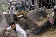 A bulldozer is used to clear a street of debris beside the crater where the home of Ramez al-Masri was destroyed by an air-strike prior to a cease-fire reached after an 11-day war between Gaza's Hamas rulers and Israel, Sunday, May 23, 2021, in Beit Hanoun, the northern Gaza Strip. (AP Photo/John Minchillo)