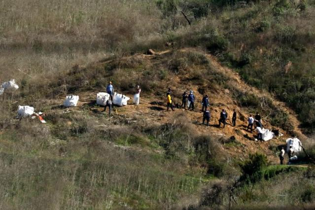 FILE PHOTO: Personnel collect debris while working with investigators at the helicopter crash site of NBA star Kobe Bryant in Calabasas, California