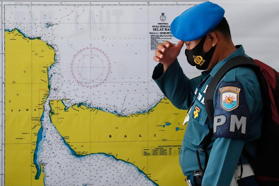 <p>A military officer stands in front of a map of the search area for the missing Indonesian Navy submarine KRI Nanggala 402</p> (EPA)