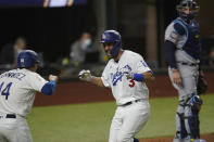 Los Angeles Dodgers' Chris Taylor celebrates a two-run home run with Enrique Hernandez against the Tampa Bay Rays during the fifth inning in Game 2 of the baseball World Series Wednesday, Oct. 21, 2020, in Arlington, Texas. (AP Photo/Eric Gay)