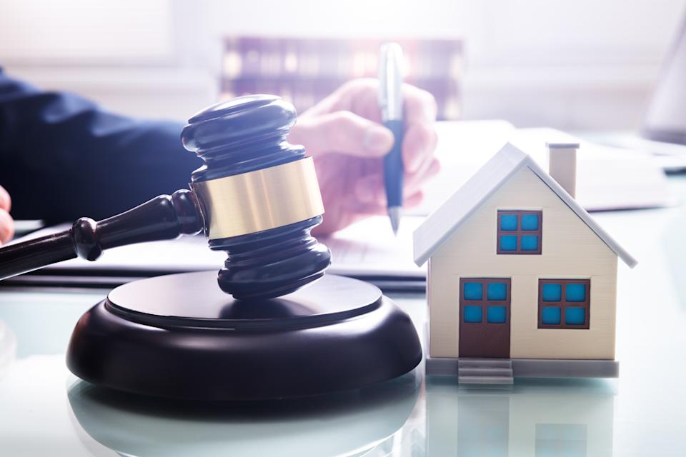 Gavel With Sound Block And House Model Over Desk In Front Of A Businessperson