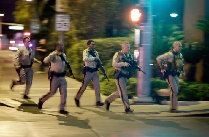 """FILE - In this Oct. 1, 2017, file photo, police run toward the scene of a shooting near the Mandalay Bay resort and casino on the Las Vegas Strip in Las Vegas. A public panel planning a permanent Las Vegas memorial honoring victims of the deadliest mass shooting in modern U.S. history heard that there's no perfect answer to how a tribute should look and feel. """"The goal is to provide comfort and hope and facilitate healing,"""" Anita Ahuja, manager of mass violence response for the California Victim Compensation Board, advised the 1 October Memorial Committee during its initial meeting Nov. 25, 2020. (AP Photo/John Locher, File)"""