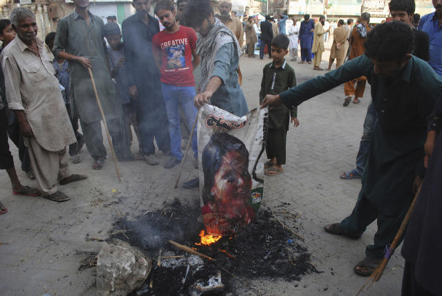 FILE - In this Nov. 1, 2018, file photo, Pakistani protesters burn a poster showing Aasia Bibi, in Hyderabad, Pakistan. In Mid January 2019, Bibi, a Pakistani Christian woman, still lives the life of a prisoner, although she was freed from death row by the country's top court more than two months ago. Meanwhile, a petition by Islamist radicals who rallied against her acquittal of blasphemy charges and who seek her execution awaits a Supreme Court decision. (AP Photo/Pervez Masih, File)