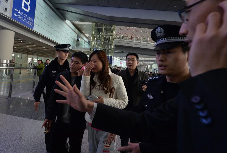 A woman cries at Beijing Airport after news of the missing Malaysia Airlines Boeing 777-200 plane is announced on March 8, 2014