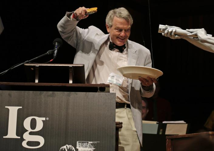 CORRECTS TO REMOVE REFERENCE TO KIRSHER WINNING 2011 NOBEL PRIZE FOR PHYSICS, ADDS HIS CURRENT TITLE - Harvard University Clowes Professor of Science Robert Kirshner holds up a piece of pie while explaining a pie chart about the universe, shortly before eating it, during a performance at the Ig Nobel Prize ceremony at Harvard University, in Cambridge, Mass., Thursday, Sept. 20, 2012. The Ig Nobel prize is an award handed out by the Annals of Improbable Research magazine for silly sounding scientific discoveries that often have surprisingly practical applications. (AP Photo/Charles Krupa)