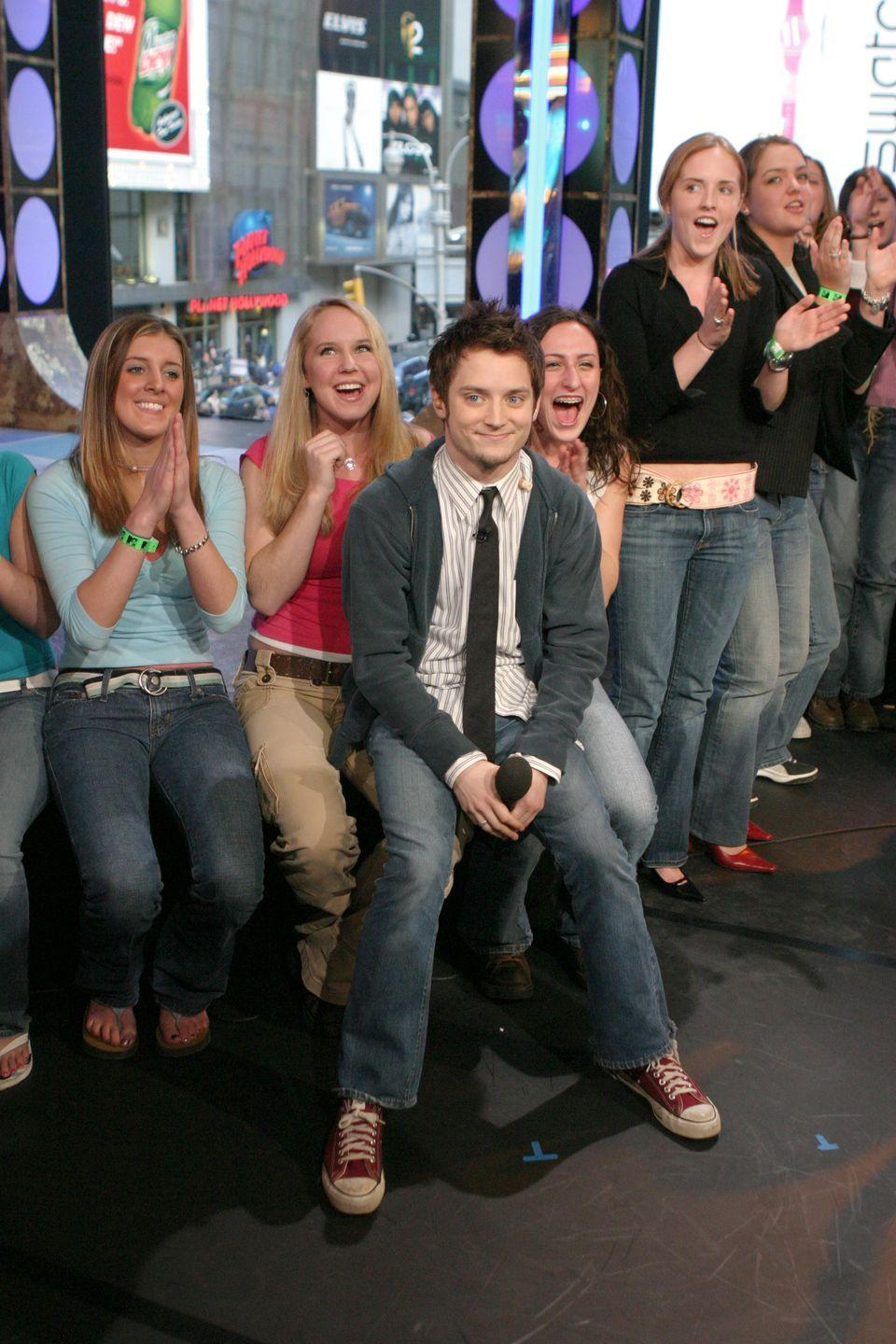 <p>Just Elijah Wood promoting <em>The</em> <em>Lord of the Rings</em> while wearing high water bootcut jeans and sitting on these girls' laps, don't even worry about it. </p>