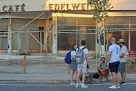 """Visitors in front of the dilapidated """"Edelweiss"""" cafe in the fenced-off area of Varosha"""