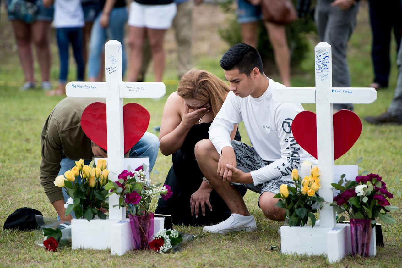 <p>People visit a cross for Christopher Stone at a memorial for the victims of the Santa Fe High School shooting on May 21, 2018 in Santa Fe, Texas. (Photo: Brendan Smialowski/AFP/Getty Images) </p>