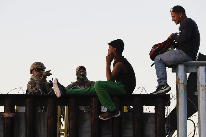 <p>U.S. Border Patrol agents, left, speak with two Central American migrants as they sit atop the border structure separating Mexico and the United States, Wednesday, Nov. 14, 2018, in Tijuana, Mexico. Migrants in a caravan of Central Americans scrambled to reach the U.S. border, catching rides on buses and trucks for hundreds of miles in the last leg of their journey Wednesday as the first sizable groups began arriving in the border city of Tijuana. (Photo: Gregory Bull/AP) </p>