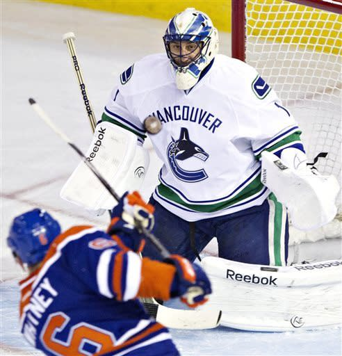Vancouver Canucks goalie Roberto Luongo makes the save on Edmonton Oilers' Ryan Whitney (6) during the second period of an NHL hockey game in Edmonton, Alberta, on Saturday, March 30, 2013. (AP Photo/The Canadian Press, Jason Franson)
