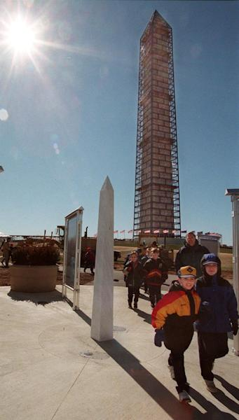 FILE - This Feb. 22, 1999 file photo shows a group leaving after touring the scaffold shrouded Washington Monument in Washington, as the monument opened for the first time in four months. The interior was closed to allow workers unhindered time to erect a metal and fabric web of scaffolding that now robes the 555-foot obelisk. Crews are fixing the monument's aging joints, repairing cracked and chipped stones and cleaning the entire exterior surface. Repairs to the Washington Monument will require massive scaffolding to be built around the 555-foot obelisk and may keep it closed until 2014 after it was damaged by an earthquake last year. (AP Photo/Kamenko Pajic, File)