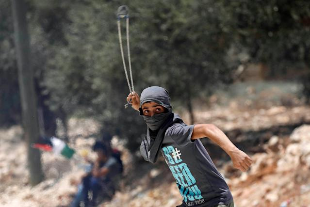 A Palestinian uses a sling to hurl stones towards Israeli troops during a protest near the Jewish settlement of Qadomem, in village of Kofr Qadom near Nablus in the occupied West Bank June 22, 2018. REUTERS/Mohamad Torokman TPX IMAGES OF THE DAY