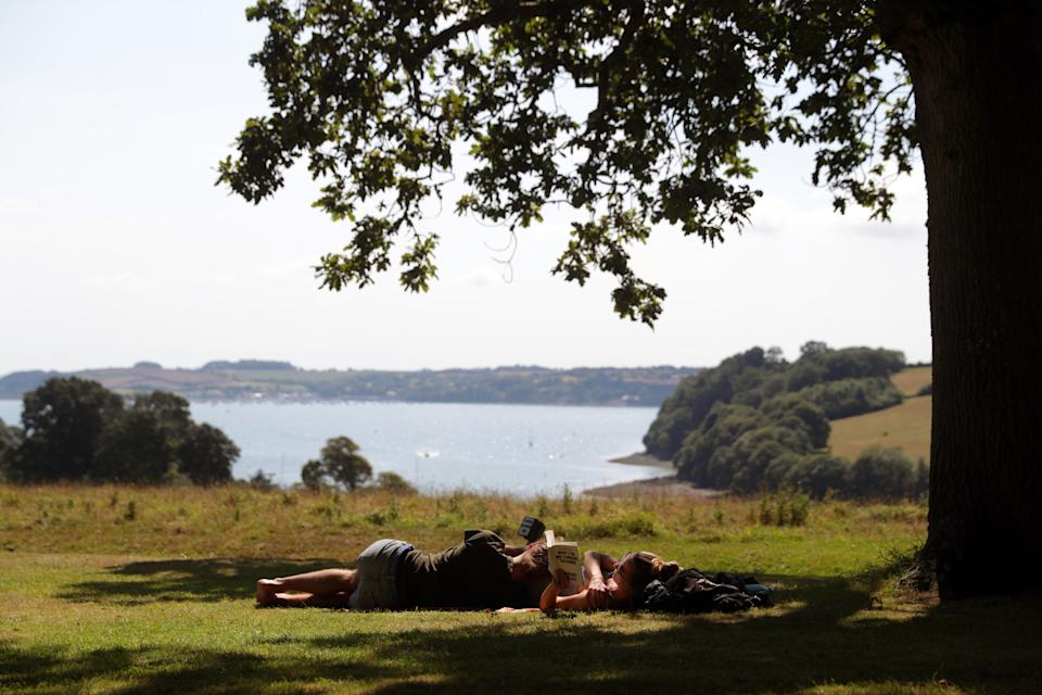 People find shade under a tree at the National Trust's, Trelissick Garden, in Cornwall, as the UK could see record-breaking temperatures with forecasters predicting Friday as the hottest day of the year.