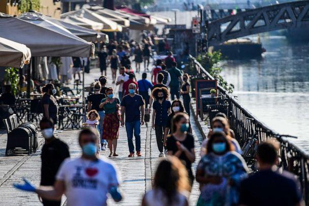 PHOTO: People stroll along a canal in the Navigli district of Milan, Italy, on May 21, 2020, as the country eases a monthslong lockdown aimed at curbing the spread of the novel coronavirus. (Miguel Medina/AFP via Getty Images)