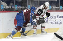 Colorado Avalanche left wing Andre Burakovsky, left, fights for control of the puck with Arizona Coyotes defenseman Jason Demers in the first period of an NHL hockey game Monday, March 8, 2021, in downtown Denver. (AP Photo/David Zalubowski)