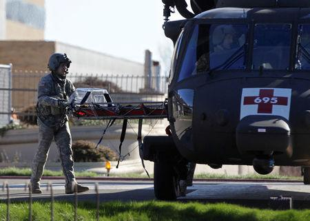 An Oregon Army National Guard Black Hawk helicopter crew member returns with a stretcher after a rescue from Mount Hood, at Legacy Emanuel Medical Center in Portland, Oregon, U.S., February 13, 2018. REUTERS/Steve Dipaola