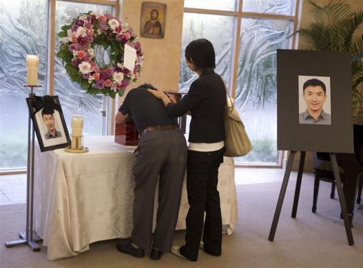 Dirang Lin (L), father of slain student Jun Lin is overcome as he hugs the urn prior to funeral services in Montreal, July 26, 2012.