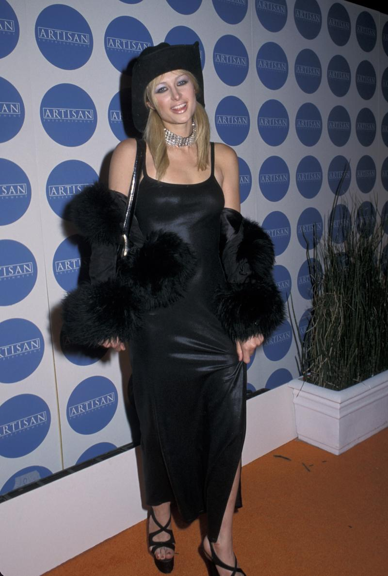 Last but not least: Paris Hilton wears a black slip dress, fur coat, and cowboy hat on the red carpet in the 2000s.